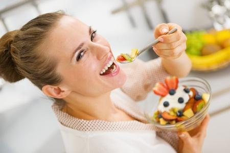 ätande: Lycklig ung hemmafru äta frukt sallad. bakifrån