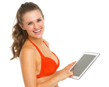 Smiling young woman in swimsuit using tablet pc Stock Photo - 20542751
