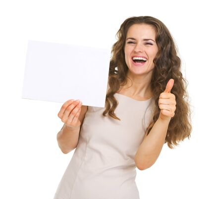 Smiling young woman showing blank paper and thumbs up Stock Photo - 20671419
