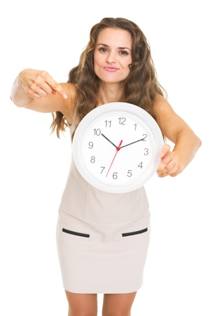 disquieted: Concerned young woman pointing on clock Stock Photo