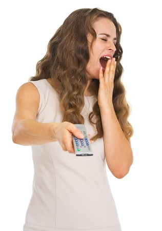 yawing: Yawing young woman switching channels with tv remote control
