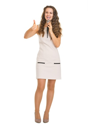Full length portrait of smiling young woman with microphone showing thumbs up Stock Photo - 20857133