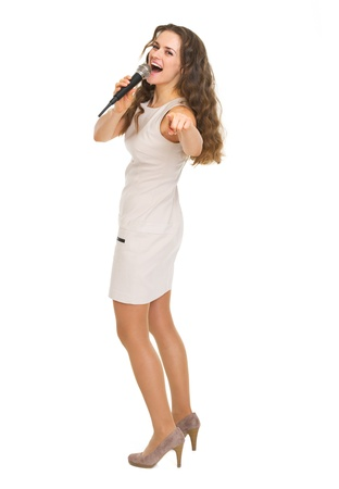 Full length portrait of happy young woman with microphone pointing in camera Stock Photo - 20857135