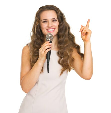 Smiling young woman with microphone pointing up on copy space Stock Photo - 20857136
