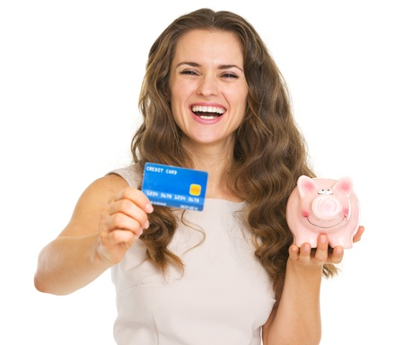 frugality: Happy young woman showing credit card and piggy bank