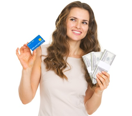Thoughtful young woman with credit card and dollars looking on copy space Stock Photo - 20671431