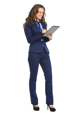 Full length portrait of happy business woman working with tablet pc photo
