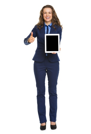 Full length portrait of smiling business woman showing tablet pc blank screen photo