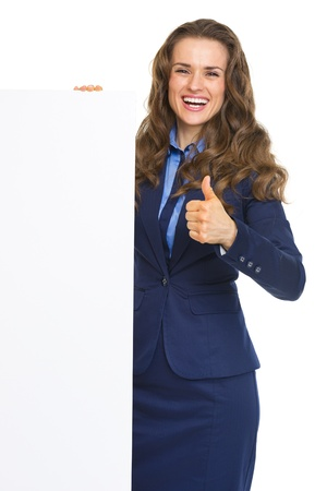 Happy business woman showing blank billboard and thumbs up photo