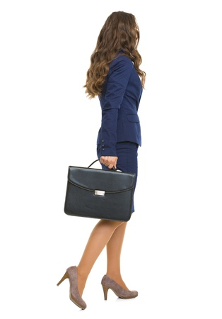 business costume: Full length portrait of business woman with briefcase going . rear view