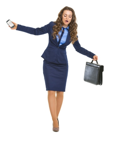 disquieted: Concerned business woman with briefcase and cell phone balancing on dangerous path