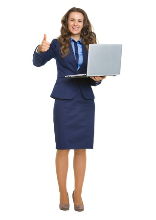 Full length portrait of smiling business woman with laptop showing thumbs up photo