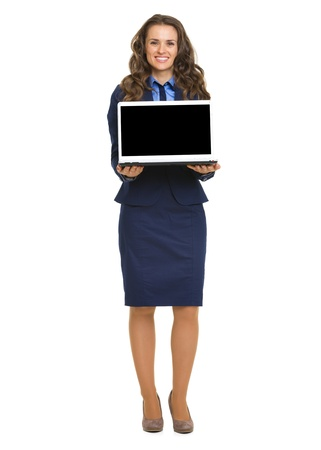 Full length portrait of happy business woman showing laptop blank screen Stock Photo - 21250420