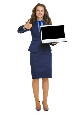 Happy business woman showing laptop blank screen and thumbs up photo