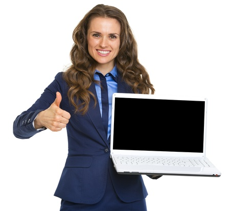 Smiling business woman showing laptop blank screen and thumbs up photo
