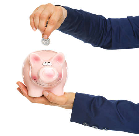 Closeup on business woman hands putting coin into piggy bank Stock Photo - 21250487