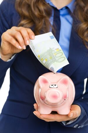Closeup on business woman putting 100 euro banknote into piggy bank Stock Photo - 21250489