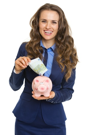 Smiling business woman putting 100 euro banknote into piggy bank Stock Photo - 21250490