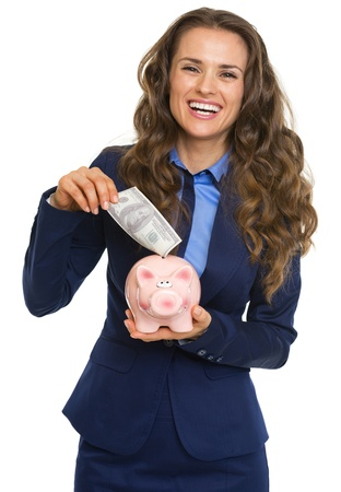 Smiling business woman putting 100 dollars banknote into piggy bank Stock Photo - 21250492