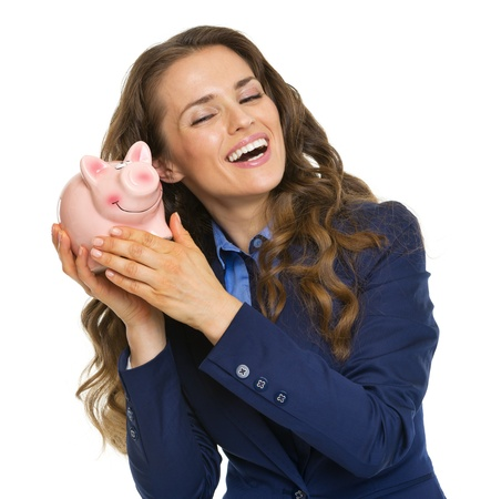 Happy business woman listening whats inside piggy bank Stock Photo - 21250499