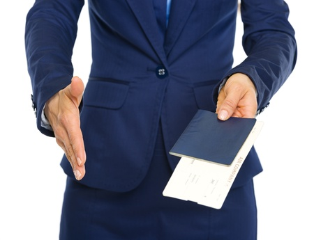 Closeup on business woman giving passport with air tickets and stretching hand for handshake photo
