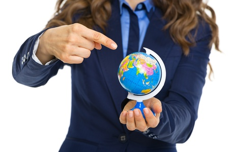 Closeup on business woman pointing on earth globe photo