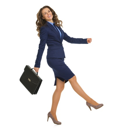 cheerfully: Full length portrait of smiling business woman with briefcase cheerfully going sideways