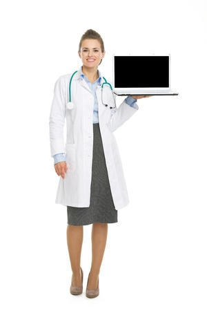 Full length portrait of happy doctor woman showing laptop blank screen Stock Photo - 21250589
