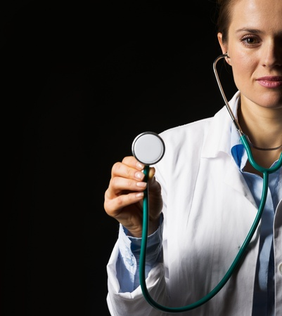Doctor woman using stethoscope isolated on black Stock Photo - 21250631