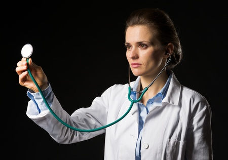 Doctor woman using stethoscope isolated on black Stock Photo - 21250633