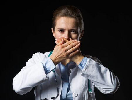 Portrait of doctor woman showing speak no evil gesture isolated on black