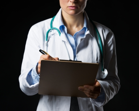 Closeup on doctor woman writing in clipboard isolated on black photo