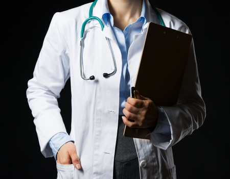 Closeup on doctor woman with clipboard isolated on black photo
