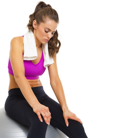 Tired young woman sitting on fitness ball Stock Photo