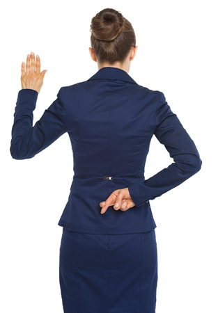 double game: Business woman holding crossed fingers behind back while oath truth . rear view