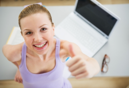 erudition: Smiling young woman studying in kitchen and showing thumbs up Stock Photo