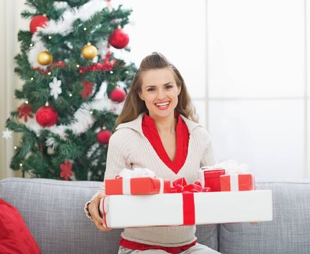 Portrait of happy young woman with christmas present boxes near christmas tree Stock Photo - 21353228