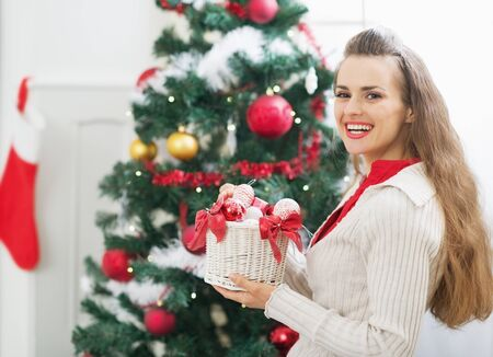 Smiling young woman with christmas decorations near christmas tree Stock Photo - 21353281