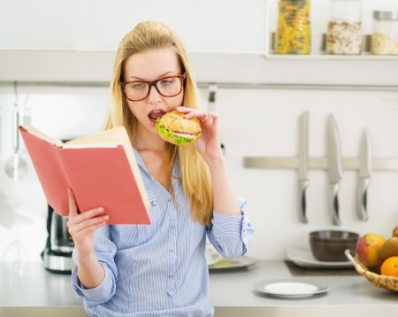 Teenager girl having burger in kitchen while studying Stock Photo