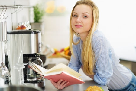 classbook: Teenager girl reading book in kitchen