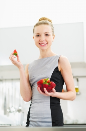 Young housewife eating strawberry in modern kitchen photo