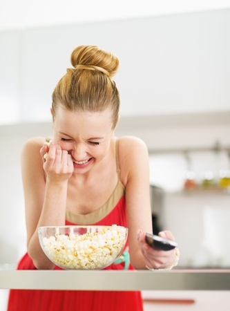 Laughing young woman eating popcorn and watching tv in kitchen photo