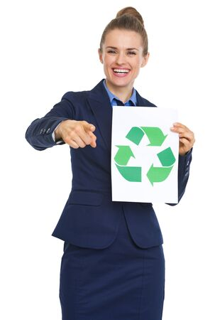 Smiling business woman showing recycle sign and pointing in camera photo