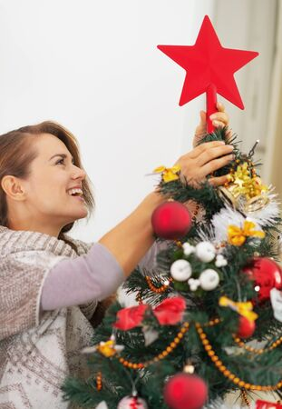 Happy young woman setting top on christmas tree Stock Photo - 21353800