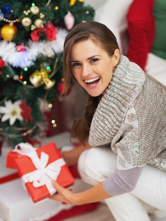Happy young woman with christmas present box near christmas tree Stock Photo - 21353820
