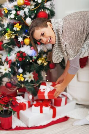 Happy young woman taking christmas present box from under christmas tree Stock Photo - 21353821