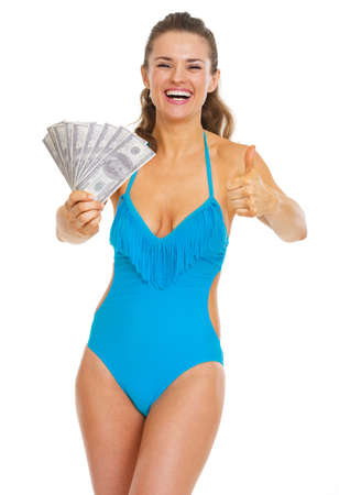 Smiling young woman in swimsuit showing fan of dollars and thumbs up Stock Photo - 21353856