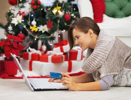 Happy young woman with credit card using laptop near christmas tree Stock Photo - 21353879