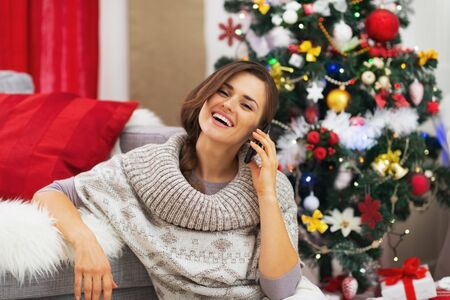 Happy young woman talking mobile phone near christmas tree Stock Photo - 21353881