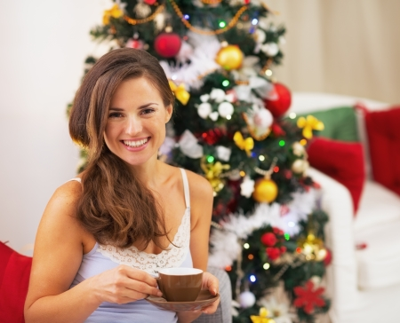Happy young woman in pajamas near christmas tree drinking hot beverage